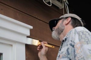 Painter Appying Exterior Paint to Wood Surface | Slatter HOA Management | Greensboro